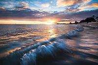 A colorful sunset illuminates a small wave washing up against the shore of Ala Moana Beach, O'ahu.