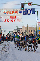 Musher Martin Buser and Iditarider Peter Stephens.leave the 2011 Iditarod ceremonial start line in downtown Anchorage, Alaska