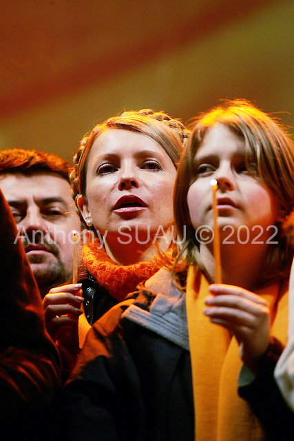 """Kiev, Ukraine.December 28, 2004..The political partner of opposition candidate Viktor Yushchenko, Yulia Timoshenko on Maidan Independence Square as thousands of Orange flag waving supporters rally to their side...Election polls show him as a clear winner however he has not yet been declared the winner nor has his opponent refuses to admit defeat...The first round of voting was considered fraudulent when the ruling president Viktor Yahukovich won and the opposition candidate Viktor Yushchenko lost. ..Several hundred thousand Ukrainians took to the streets of Kiev and held daily rallies on Maidan Independence Square. The protests lasted nearly a month before the first vote was declared invalid and a new round of elections held on December 26, 2004. ..The demonstrations would come to be known as the """"Orange Revolution"""" after the color of the opposition party."""