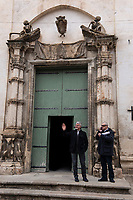 Italy. Apulia Region. Gravina in Puglia. Vescovado is a  Roman Catholic church. Two men stand in front of the church's main entrance, One man waves his right hand, the other speaks on his mobile phone. Above the door, the sculptures of two old human skeletons. Gravina in Puglia is a town in Apulia (Puglia) which is a region in Southern Italy. 8.12.18  © 2018 Didier Ruef