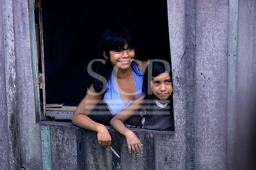 Manaus, Brazil. Two girl seamstresses at the window of their shack.