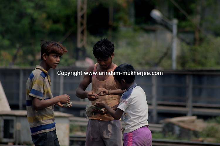 Alamgir and his friends at the Sealdah railway premises. He is staying here for last 6 years from the time he ran away from his home due to domestic violence and poverty. As per his version his father was a drunkard and used to beat his mother for no reason. His father even could not earn enough money to buy food for their big family. Due to this traumatic situation he ran away from house at the age of seven. Ever since, the Sealdah railway station in Kolkata has been his home. As far as company is concerned, he had not much reason to miss his family. There are around 500 children, from 5 to 16 years, who live in the premises of Kolkata's second largest train terminus. Most of them addicted to Brown Sugar and sniffing industrial adhesive Dendrite. They say they don't feel hungry if they take the drugs. Their presence is conspicuous, even in a place that registers an average footfall of 1.4 million on weekdays. Their activities cover a wide range, from begging, to pulling handcarts, to petty theft, to selling odds and ends on the platform or on trains. The money, earned or ill-gotten as the case may be, is spent in procuring heroin, brown sugar, cocaine, and tubes of Dendrite. Calcutta, West Bengal, India. Arindam Mukherjee