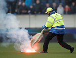 Falkirk steward attacks the flare with a bucket of sand but misses most of it as it burns through the plastic surface.