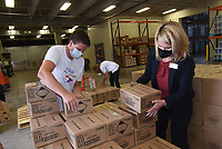 HANDS-ON DONATION<br />Brennan HIle (left)  with Live Clean hand sanitizer and Dr. Janet Schwanhausser, Bentonville deputy school superintendent, stack boxes containing 50,000 bottles of hand sanitizer donated to the region's schools by Live Clean hand-sanitizer company. Boxes of hand sanitizer were unloaded for storage at the Bentonville School District facilities building. Bottles of various sizes will be distributed to 54 area schools, said Leslie Godwin with Live Clean. Hand sanitizer is not normally in the district's budget, Schwanhausser said, so the donation will free up funds to purchase other items that students need. Go to nwaonline.com/200915Daily/ to see more photos.<br />(NWA Democrat-Gazette/Flip Putthoff)