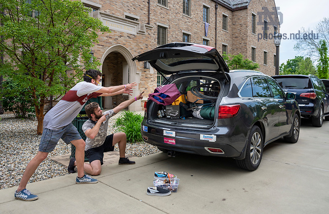 May 27, 2020; Owen Kranz sophomore student of Aerospace, Aeronautical and Astronautical Engineering,  (left) tosses the last bag of belongings from his dorm into his SUV as his brother Aidan assists. Kranz moved out of Knott Hall.  (Photo by Barbara Johnston/University of Notre Dame)