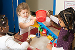 Preschool 2-3 year olds sand table group of three girls playing together pouring sand