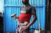 A recycling worker prepares to use a hammer to break down electronics in a market in central Kolkata, India. November, 2013