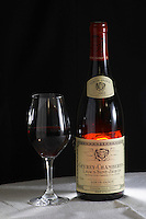 A bottle of Maison Louis Jadot Gevrey Chambertin Lavaux Saint St Jacques 2002 Premier 1er Cru red burgundy wine and a glass of red wine standing on a table top with a white cloth. Backlit backlight back light lit Black background, Maison Louis Jadot, Beaune Côte Cote d Or Bourgogne Burgundy Burgundian France French Europe European