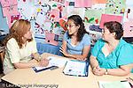 Group of three female preschool teachers conferring, meeting and talking