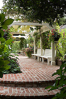 Brick path and steps leading to pergola covering benches in organic California garden