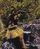 Hand-tinted historical photo of a Hawaiian hula dancer playing her ukulele near a stream