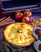 Apple pie, showing oven in background with red apples and cinnamon sticks