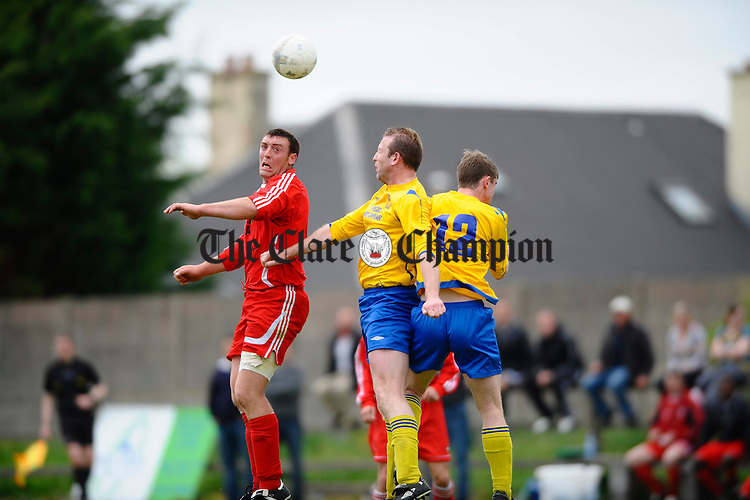 Burren United's John Mc Donagh contests a ball with Nwtown's Noel Donnellan and Ray Quigley  during their Munster Junior Cup Clare Area Final at Doora. Photograph by John Kelly.
