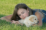 Teenage girl sleeping while yellow Labrador retriever (AKC) puppy sneaks off