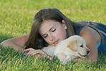 Teenage girl sleeping while yellow Labrador retriever (AKC) puppy sneaks off