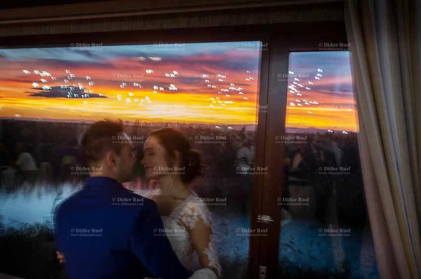 """Spain. Valencia Province. Valencia. Nou Racó restaurant. Wedding of Gaetano & Raquel. An intimate moment for bride and groom. Colorful sunset over the Albufera, or L'Albufera de València ([albuˈfeɾa], meaning """"lagoon"""" in Valencian), is a freshwater lagoon and estuary on the Gulf of Valencia coast. It is the main portion of the Valencian Albufera Natural Park, with a surface area of 21,120 hectares (52,200 acres). The natural biodiversity of the nature reserve allows a great variety of flora and fauna to thrive. Though once a saltwater lagoon, dilution due to irrigation and canals draining into the estuary and the sand bars increasing in size had converted it to freshwater by the seventeenth century. Valencia (officially València) is the capital of the autonomous community of Valencia and the third-largest city in Spain. 15.12.18  © 2018 Didier Ruef"""