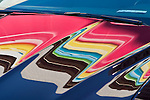Cars parked in parking lot with colors reflected onto winshiled and car hood