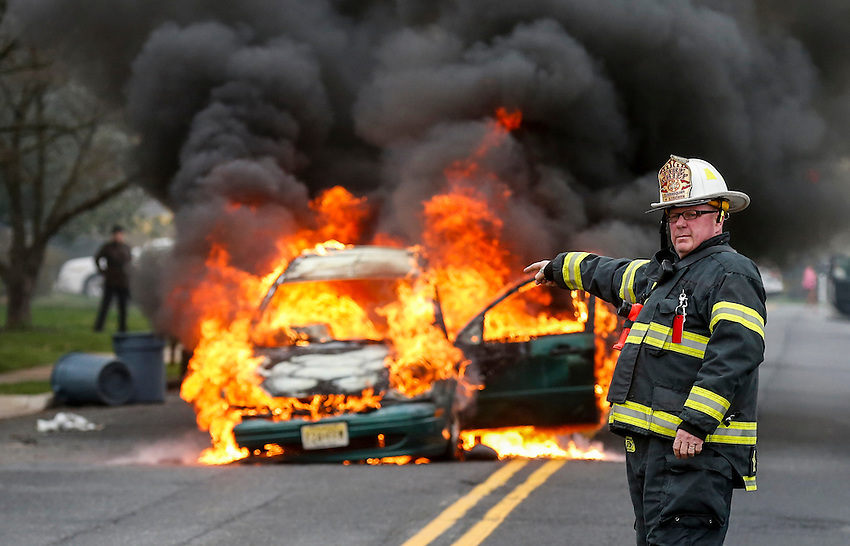 MANASQUAN, NJ — April 1, 2016 —Manasquan fire chief Dave Kircher directs the first responding engine to the scene as a 2000 Ford Focus becomes fully engulfed in flames about 9:40am on Broad Street, here. The driver of the vehicle, Nancy Trapani of Belmar, was not injured.  photo by Andrew Mills