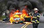 MANASQUAN, NJ — April 1, 2016 — Manasquan fire chief Dave Kircher directs the first responding engine to the scene as a 2000 Ford Focus becomes fully engulfed in flames about 9:40am on Broad Street, here. The driver of the vehicle, Nancy Trapani of Belmar, was not injured.  photo by Andrew Mills