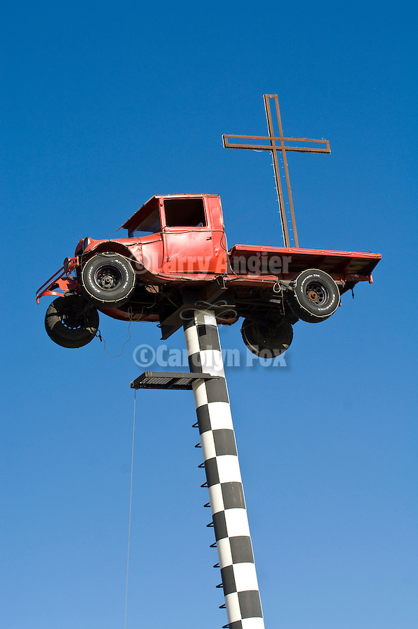 Red Model A Ford flatbed truck on black and white checkered pole, cross on the bed (sign for welding shop)