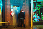 """© Joel Goodman - 07973 332324 . 17/12/2016 . Manchester , UK . A man is illuminated by the blue lights of a police van as he is caught urinating in a doorway on Deansgate . Revellers out in Manchester City Centre overnight during """" Mad Friday """" , named for being one of the busiest nights of the year for the emergency services in the UK . Photo credit : Joel Goodman"""