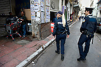 A police man and woman inpect two men hanging out on a street. Not long after, the men are arrested.