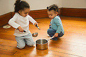 MR / Schenectady, NY. Young children (sisters; aged 1 and 3; African-American and Caucasian) use a pot and spoons as toys to play with, pretending they are making food. MR: Dal4, Dal5. ID: AM-HD. © Ellen B. Senisi