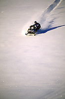 A snowmobile travels down a snow-covered hill.