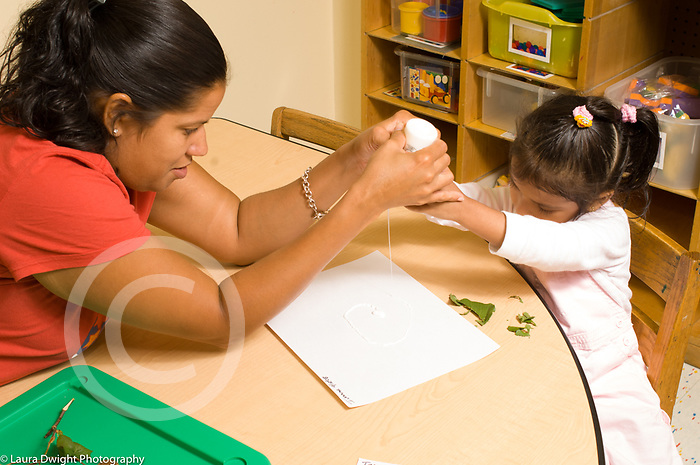 preschool 2-3 year olds science nature observation female teacher helping girl with glue bottle preparing to glue leaf fragments to paper