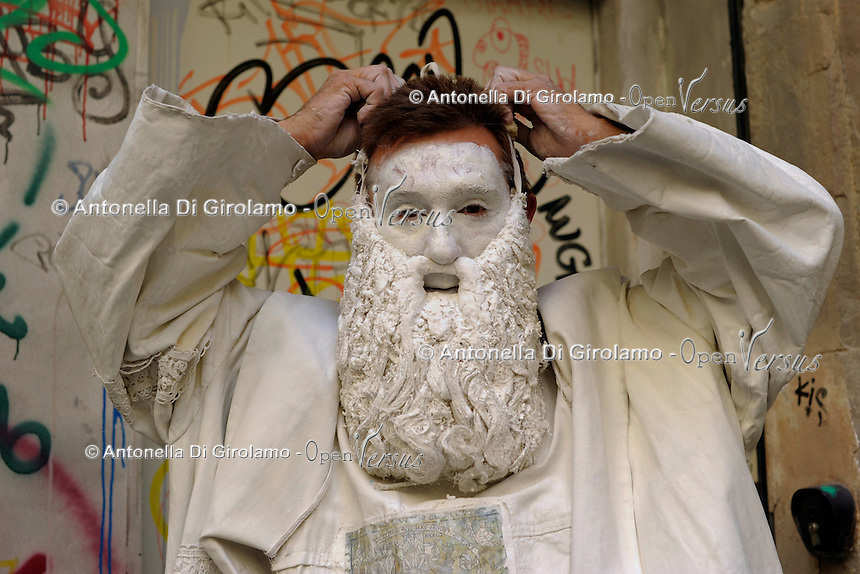 Statua vivente raffigurante Leonardo da Vinci. Il mimo Valter Conti  mentre si dedica al suo make up e mentre si veste per la sua esibizione. Resterà immobile stuzzicando la curiosità dei turisti con biglietti con frasi di Leonardo, a Firenze. Living statue of Leonardo da Vinci.The mime Valter Conti   while he is dedicating to his make up and while he dresses for the performance. He Will  tickling the curiosity of tourists with tickets of sentences by Leonardo, in Florence.