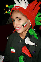 Young girl smiling in her costume celebrating the Independence Day of Kuwait.  Flag colors on her face.