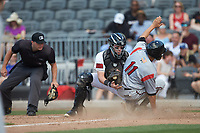 Fayetteville Woodpeckers catcher Michael Papierski (28) attempts to apply a tag to Ryan Aguilar (11) of the Carolina Mudcats as home plate umpire Jake Bruner looks on at SEGRA Stadium on May 18, 2019 in Fayetteville, North Carolina. The Mudcats defeated the Woodpeckers 6-4. (Brian Westerholt/Four Seam Images)