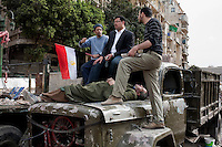 Anti Governemnt protesters take a break and talk on top of a burnt out, abandoned army truck in Tahrir Square, the scene of heavy clashes between pro and anti government protesters. Continued anti-government protests take place in Cairo calling for President Mubarak to stand down. After dissolving the government and allowing for talks with opposition parties Mubarak still refuses to step down from power...