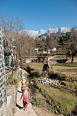 Dharamsala, Himachal Pradesh, India. Women workers carrying baskets of sand on their heads along a narrow path.