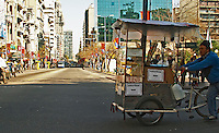 A cityscape view of the street Avenida 18 de Julio, 18 July street, with modern office buildings and a man pushing a bicycle cart selling candied peanuts and hot water for mate herbal tea, garraninada mani calientes. Street merchant. Montevideo, Uruguay, South America