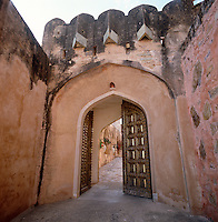 The imposing studded double doors of the gateway to this Jaipur fort which open onto a cobbled driveway through the gardens