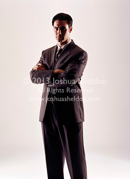 Caucasian looking man wearing a dark business suit looking forward with arms folded over his chest