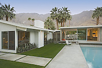 Evening view of mid-century home and pool against mountain