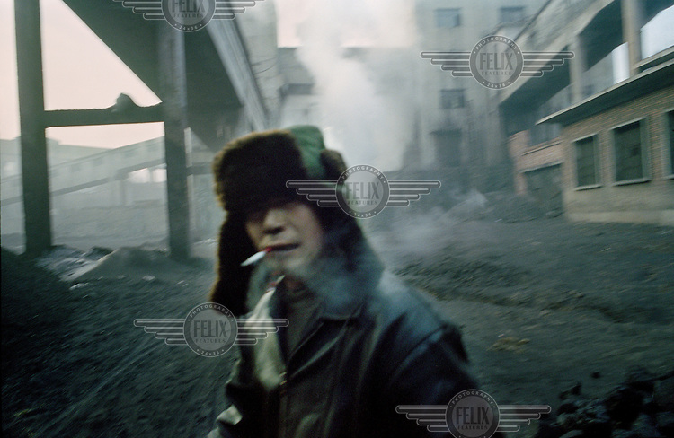 A migrant labourer smokes a cigarette at a large state-owned coal mine.  Shanxi is the largest producer of coal in China.  The rate of coal mining in the country is increasing from an annual production of over 2 billion tons in order to cater for China's rapid economic growth.