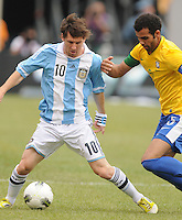 Argentina forward Lionel Messi (10) shields the ball from Brazil midfielder Sandro (5) The Argentina National Team defeated Brazil 4-3 at MetLife Stadium, Saturday July 9 , 2012.