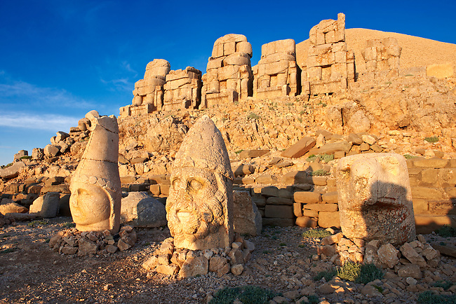Pictures of the statues of around the tomb of Commagene King Antochus 1 on the top of Mount Nemrut, Turkey. Stock photos & Photo art prints. In 62 BC, King Antiochus I Theos of Commagene built on the mountain top a tomb-sanctuary flanked by huge statues (8–9 m/26–30 ft high) of himself, two lions, two eagles and various Greek, Armenian, and Iranian gods. The photos show the broken statues on the  2,134m (7,001ft)  mountain. 2