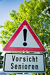 Deutschland, Bayern: Vorsicht Senioren - Verkehrszeichen in der Naehe eines Seniorenheims | Germany, Bavaria: Attention Seniors - traffic sign near a retirement home