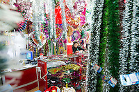November 27, 2015, Yiwu China - A vendor with Christamas tinsel on display in her small booth in the Festival Arts section of Arts of Crafts inside the Yiwu International Trade Market, where Christmas decorations are available for bulk purchase all the year round.  Yiwu International Trade Market is the world's largest whole sale market for small commodities.Photo by Dave Tacon / Sinopix
