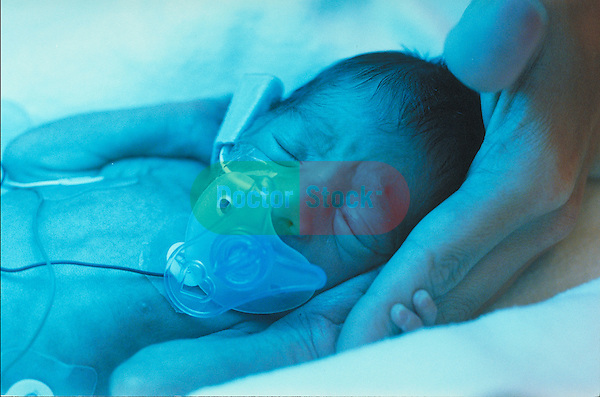 Premature infant in neonatal intensive care unit clutching hand
