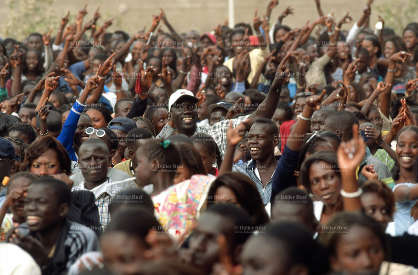Senegal. Dakar. A crowd of people attends a musical concert organised by radio Dakar, Senegal FM. People cheers, smile, wave hands and arms. © 2000 Didier Ruef