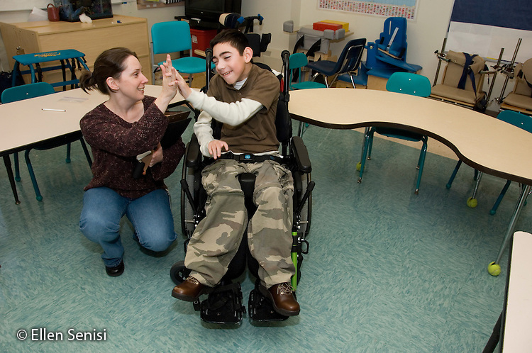 """MR / Albany, NY.Langan School at Center for Disability Services .Ungraded private school which serves individuals with multiple disabilities.Speech language pathologist and child give each other a """"high five"""" (slap hands). Boy: 11, cerebral palsy, expressive and receptive language delays.MR: Bro12; Dub1.© Ellen B. Senisi"""