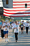 """Quad Cities Marathon 2009 """"5K"""" finish with a smile, coming home under the flag."""