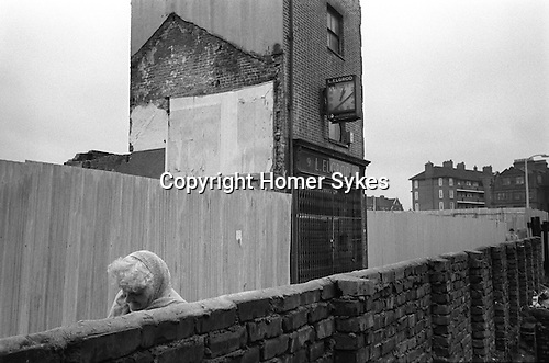 Whitechapel, London. 1975<br /> In an alley off Whitechapel High Street, head bowed against the cold, an elderly resident struggles past L. Elgrod watchmaker and jeweller, who stands alone defying the property developer and his demolition team.