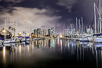 Ala Wai Harbor at night, with boats and hotels reflected in its water, Honolulu, O'ahu.