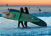 Pacific Beach, San Diego, California, USA:  Monday, January 19 2009.  A couple of surfers carry their boards out into the line up at the bottom of Loring Street.  The Martin Luther King Jnr Day holiday was marked by warm weather, big surf and a technicolored sunset as much of the rest of the country shivered in the cold.